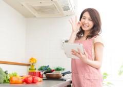タブレットを見ながら料理をする女性
